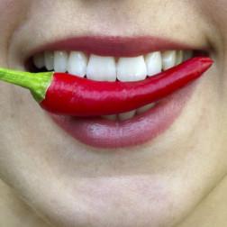 Frau mit einer Chili zwischen den Zähnen