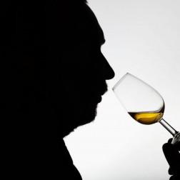 Mann riecht an einem Schnapsglas