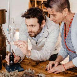Mann und Frau beim Destillieren von Kräutern