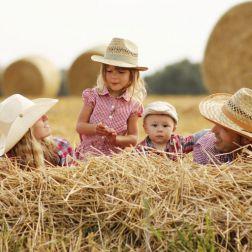Familie auf Heuhaufen mit Cowboyhüten