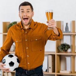 schöner Mann in modernem Wohnzimmer schreit, während er Fußball und Bier in der Hand hält