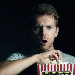 Junger Mann mit Popcorn