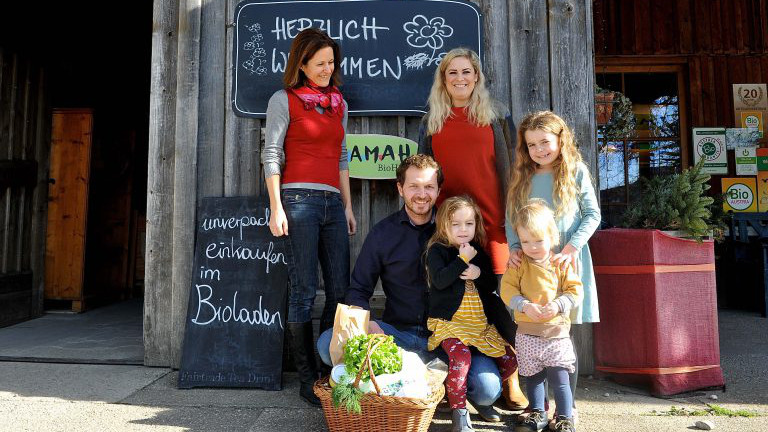 Familie mit Einkaufskorb vor dem Bioladen Adamah