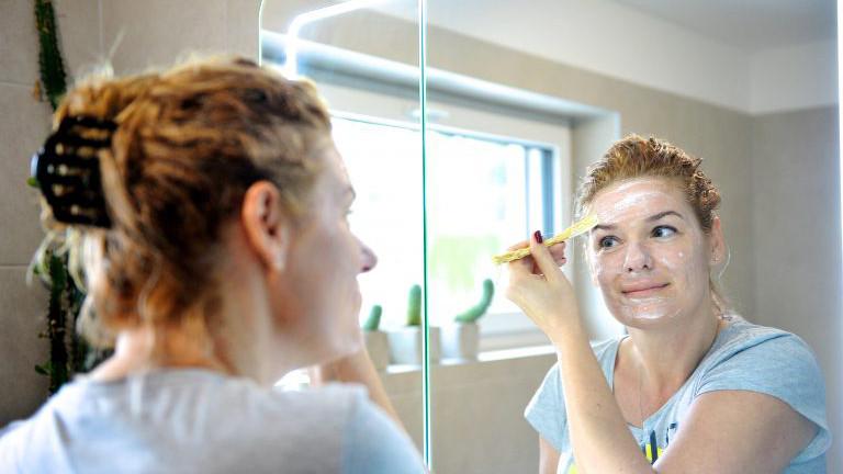 Frau vor dem Spiegel beim Auftragen einer Gesichtsmaske