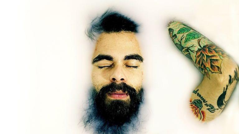 Mann mit Bart badet in Milch