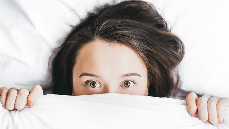Frau zieht die Bettdecke über die Nase