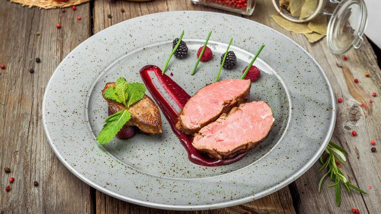 Kalbsmedaillons mit Sauce auf einem Teller. hölzerner Hintergrund