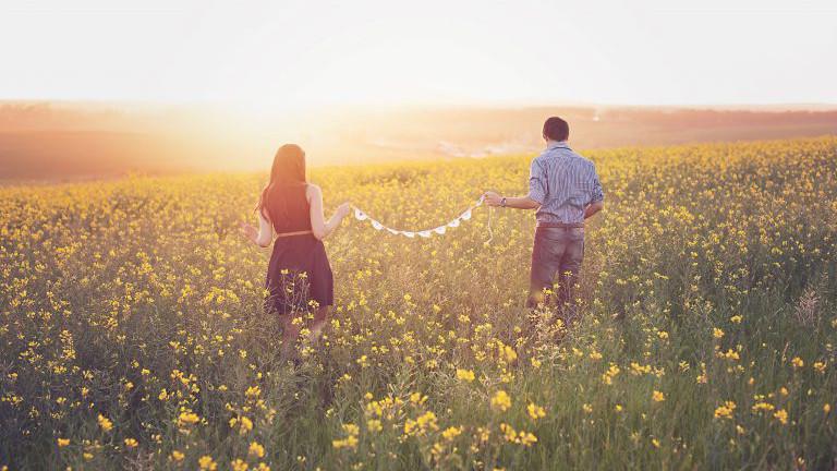 Paar im Rapsfeld bei Sonnenuntergang