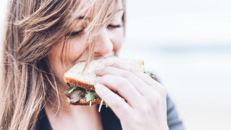 Frau isst ein Brot