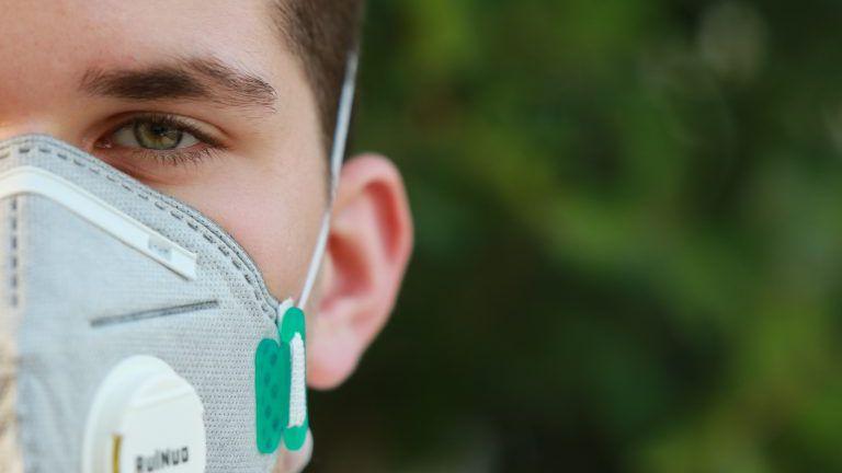 Junger Mann mit Mund-Nasenschutz