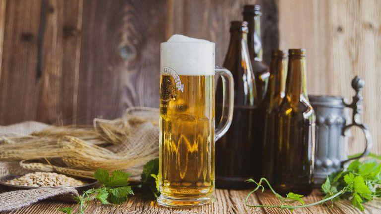 Bierglas und Flaschen auf Holztisch