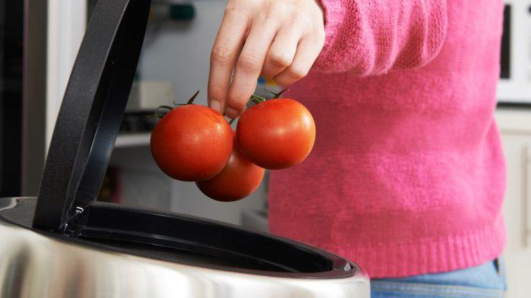 Frau wirft veraltete Lebensmittel im Kühlschrank weg
