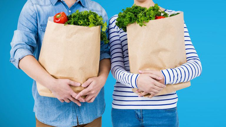 Shoppers mid sections with grocery bags against blue background
