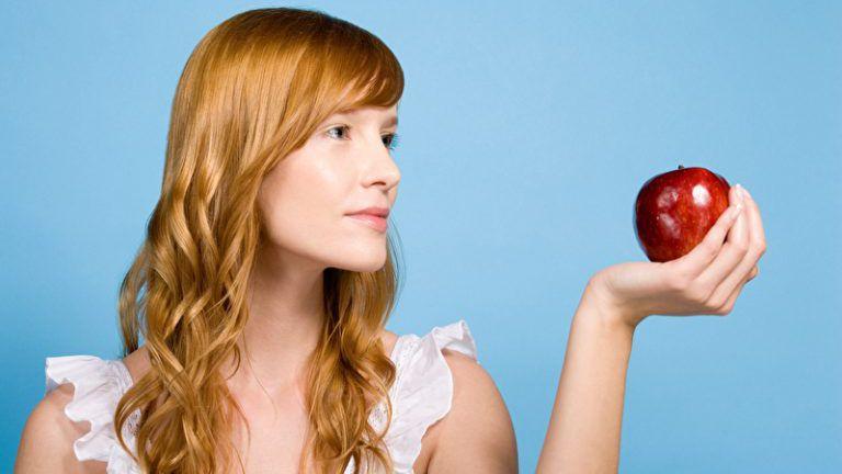 Frau hält einen Apfel
