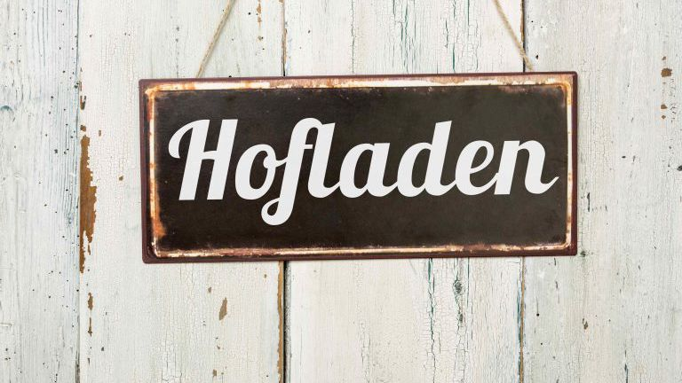Altes Blechschild vor weißer Holzwand - Hofladen