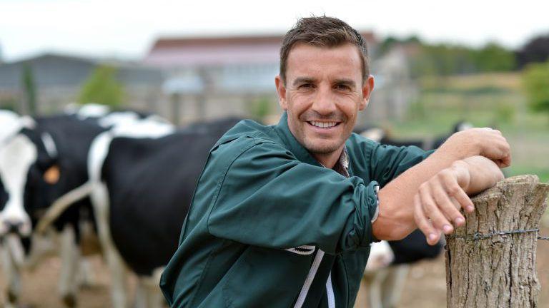 Bauer steht auf Bauernhof vor Vieh