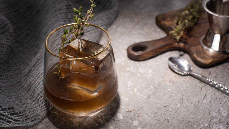 selektiver Fokus aus transparentem Glas mit Kräutern, Eiswürfeln und Whiskey auf Betonoberfläche mit Bar-Ausstattung
