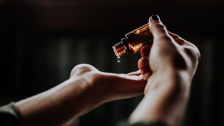 Öl tropft aus einer kleinen Flasche auf die Handfläche