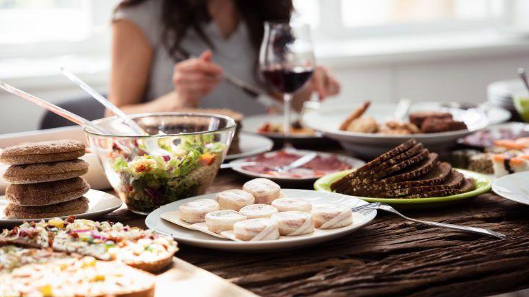 Nahaufnahme reichlich gedeckter Tisch, Lebensmittel, Frau mit Weinglas im Hintergrund