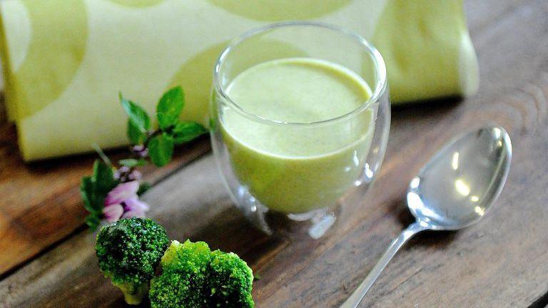 Grüne Suppe im Glas mit Brokkoli und Löffel