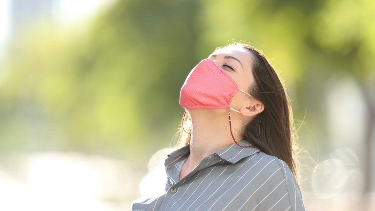 Woman wearing mask breathing fresh air in a park