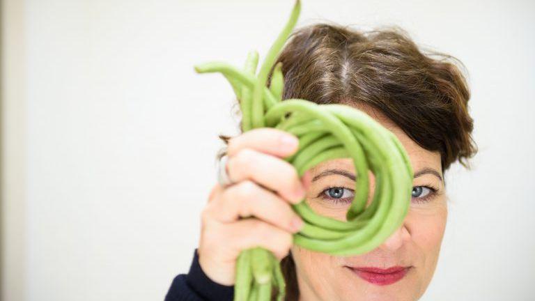 Frau schaut durch einen Ring aus Bohnen