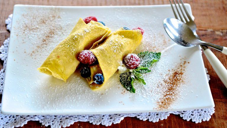 Palatschinken gefüllt mit Beeren, Teller auf einem gehäkelten Deckchen