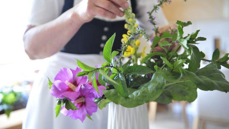 Blumenstrauß wird in einer Vase arrangiert