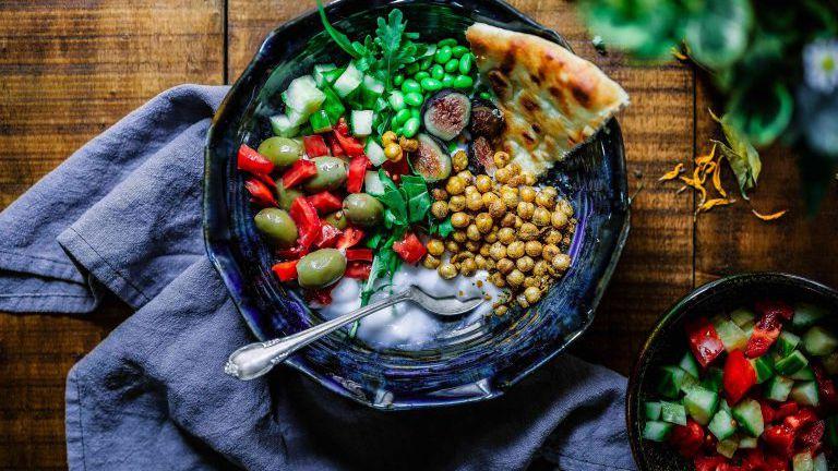 Teller mit mediterranem, vegetarischem Essen, Kichererbsen, Oliven, Brot